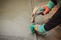 Att räffla på konkret trottoar av den använda arbetaren deformerade stålstången arkivfoto