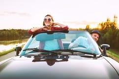Att resa vid förälskade bil- par passerar cabrioletbilen i solnedgång arkivfoton