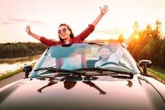 Att resa vid f?r?lskade bil- lyckliga par passerar cabrioletbilen i solnedg?ngtid royaltyfri foto