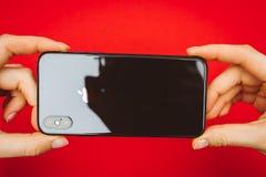 Att rymma in räcker en ny Apple Iphone X flaggskeppsmartphone Arkivfoto