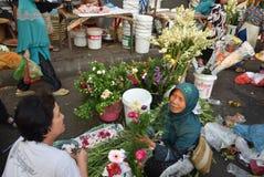 Att sälja blommar på marknaden Arkivfoto