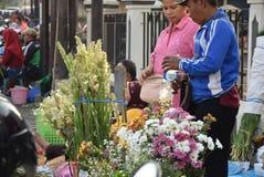 Att sälja blommar på marknaden Arkivbild