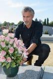 Att sätta blommar på grav Royaltyfri Fotografi