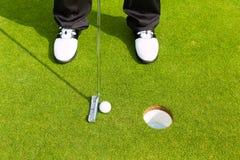 Att sätta för Golfspelare klumpa ihop sig spela golfboll i hål in Arkivfoton