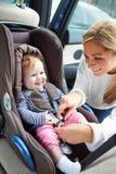 Att sätta för moder behandla som ett barn in i bilsätet Royaltyfri Foto