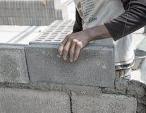 Att sätta för murare besegrar another ror av tegelstenar i plats Arkivbild