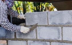 Att sätta för murare besegrar another ror av tegelstenar i plats Arkivfoto