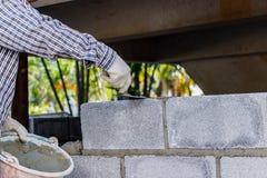 Att sätta för murare besegrar another ror av tegelstenar i plats Arkivbilder