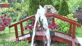 Att sakta vatten faller från en liten springbrunn i gården, bron är tillbaka stock video