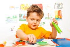 Att se den gulliga pojken som tillverkar, medan hållande, limmar arkivbilder