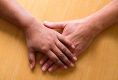 Att se ner på två händer och lägre armar förlade ontop av varje ot Royaltyfri Bild