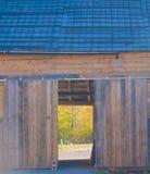 Att se till och med en öppen ladugårddörr till betar bortom arkivfoto
