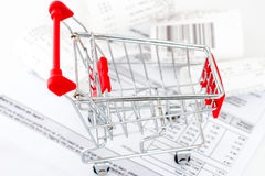 Att shoppa vagnar med boxas och pengar på en vitbakgrund Fotografering för Bildbyråer