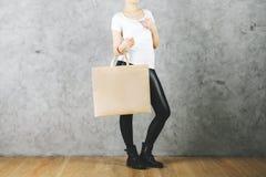 Att shoppa vagnar med boxas och pengar på en vitbakgrund Arkivfoto