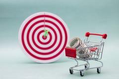 Att shoppa vagnar med boxas och pengar på en vitbakgrund Shoppingvagn och mål Royaltyfri Foto