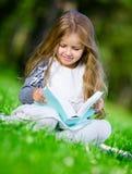 Att sitta på gräsflickan läser boken arkivfoton