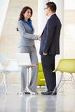 Att skaka för affärsman och för affärskvinna räcker i modernt kontor Royaltyfria Foton