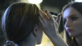 Att skjuta från tillbaka makeupkonstnär lägger över pulver med borsten lager videofilmer