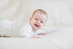 Att skratta behandla som ett barn på säng Arkivbild