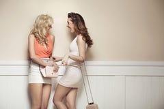 Att skratta förföriska flickvänner med sexigt lägger benen på ryggen Arkivbilder