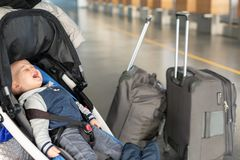 Att skrika behandla som ett barn pojken som sitter i sittvagn nära bagage på flygplatsterminalen Barn i vagn nära räknare för inc royaltyfria foton