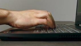 Att skriva för man fastar på bärbar datortangentbordet stock video