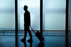 Att släpa för affärsman bär på bagageresväskan på flygplatskorridoren som går till avvikelseportar royaltyfria bilder