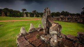 Att snida för sten av Angkor fördärvar med den stormiga skyen Royaltyfri Foto