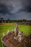 Att snida för sten av Angkor fördärvar med den stormiga skyen Arkivbilder
