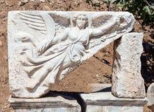 Att snida för sten av gudinnan Nike på fördärvar av forntida Ephesus, Turkiet Royaltyfri Fotografi