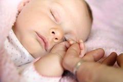 Att sova behandla som ett barn hållande moderns för flickan hand Arkivfoto