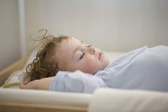 Att sova behandla som ett barn på changeren Arkivfoton