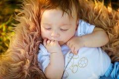 Att sova som är lurvigt, behandla som ett barn pojken som suger hans hand, närbilden, sommar Royaltyfria Bilder