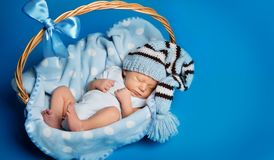 Att sova som ?r nyf?tt, behandla som ett barn, nyf?dd unges?mn i korgen, studiost?ende p? bl?tt royaltyfria foton