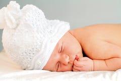 Att sova som är nyfött, behandla som ett barn flickan i vithatt Arkivbild