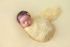 Att sova som är nyfött, behandla som ett barn flickan som lindas i guling Arkivbilder