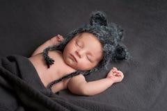 Att sova som är nyfött, behandla som ett barn pojken med Wolf Hat Arkivfoto