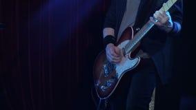 Att spela för man vaggar sång på den elektriska gitarren i nattklubb Närbild Musikerlekträelektrisk gitarr på etapp lager videofilmer