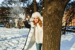 Att spela för vinterkvinna kastar snöboll utomhus- royaltyfria foton