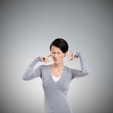 Att stänga öron med fingerkvinnan skruvniner upp henne ögon Arkivbild