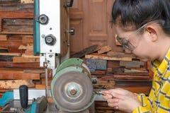 Att stå för kvinnor är att vässa drillborren på en arbetsbänk med brynemaskinen arkivfoto