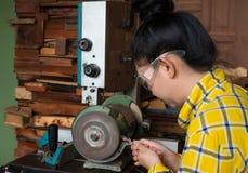 Att stå för kvinnor är att vässa drillborren på en arbetsbänk med brynemaskinen royaltyfri foto