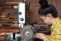 Att stå för kvinnor är att vässa drillborren på en arbetsbänk med brynemaskinen arkivbilder