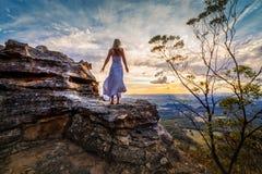 Att stå på vaggar med klänningen som blåser i vinden som hon drömmer royaltyfri fotografi