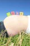 Att stava för alfabetkvarter BEHANDLA SOM ETT BARN på en gravid buk Royaltyfria Bilder