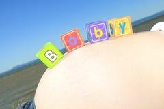 Att stava för alfabetkvarter BEHANDLA SOM ETT BARN på en gravid buk Royaltyfria Foton