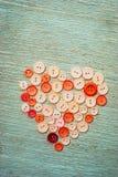 Att sy knäppas i formen av en hjärta Arkivfoto