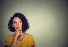 Att tänka för kvinna har många idéer som ser upp arkivfoto