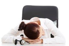 Att ta för kvinna för appellmitt ta sig en tupplur på ett skrivbord Royaltyfri Bild