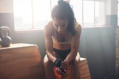 Att ta för kvinnlig idrottsman nen vilar efter konditionutbildning på idrottshallen Arkivbild